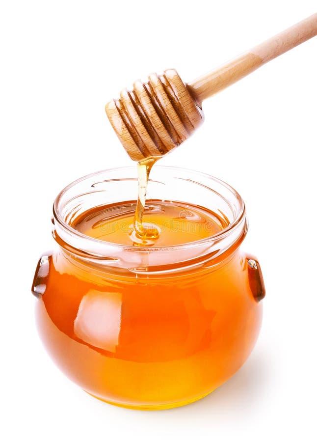 Choc en verre de miel avec le drizzler en bois photo stock