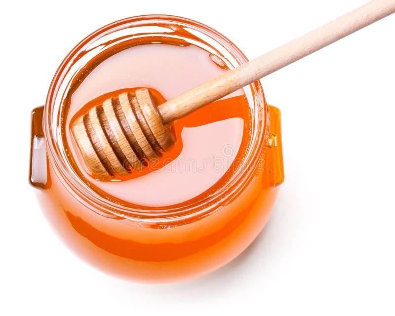Choc en verre de miel avec le drizzler en bois photographie stock libre de droits