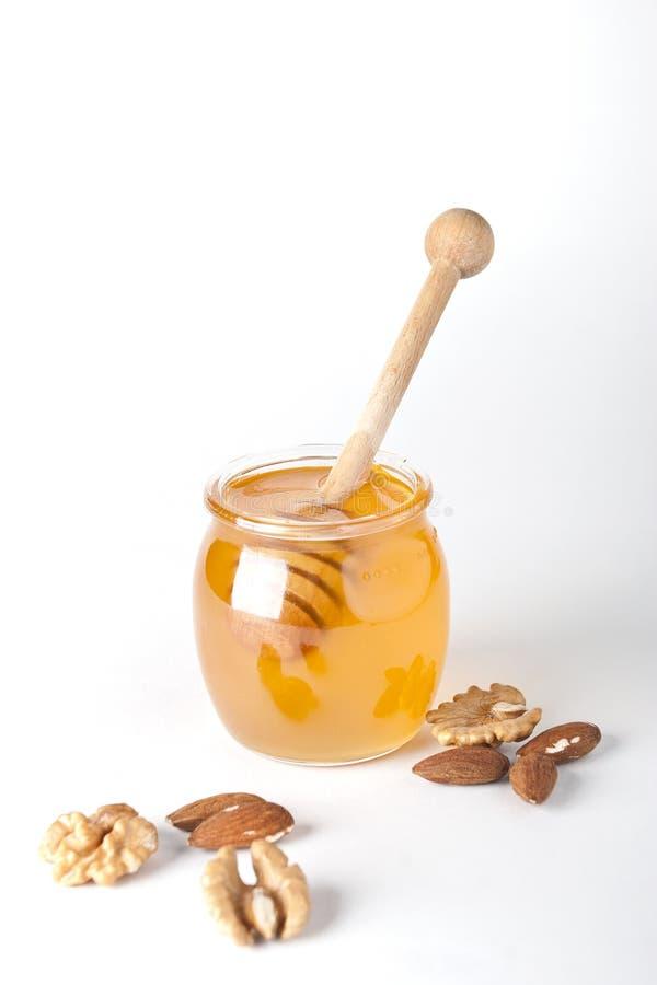 Choc en verre de miel avec le drizzler en bois photographie stock