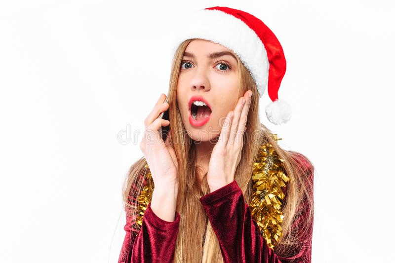 Chocado, menina no chapéu de Santa, falando emocionalmente no telefone celular imagem de stock royalty free