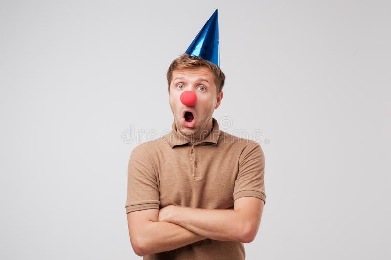 Chocan al hombre maduro en casquillo del cumpleaños y nariz roja del payaso con el regalo fotos de archivo libres de regalías
