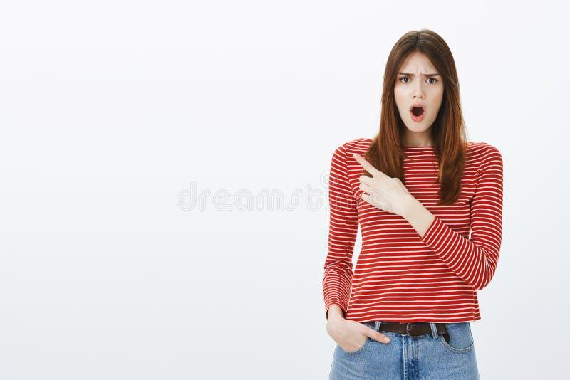 Chocan a la niñera con la desobediencia del niño, quejándose Displeased sorprendió a la mujer atractiva en la blusa rayada, cayen imagenes de archivo