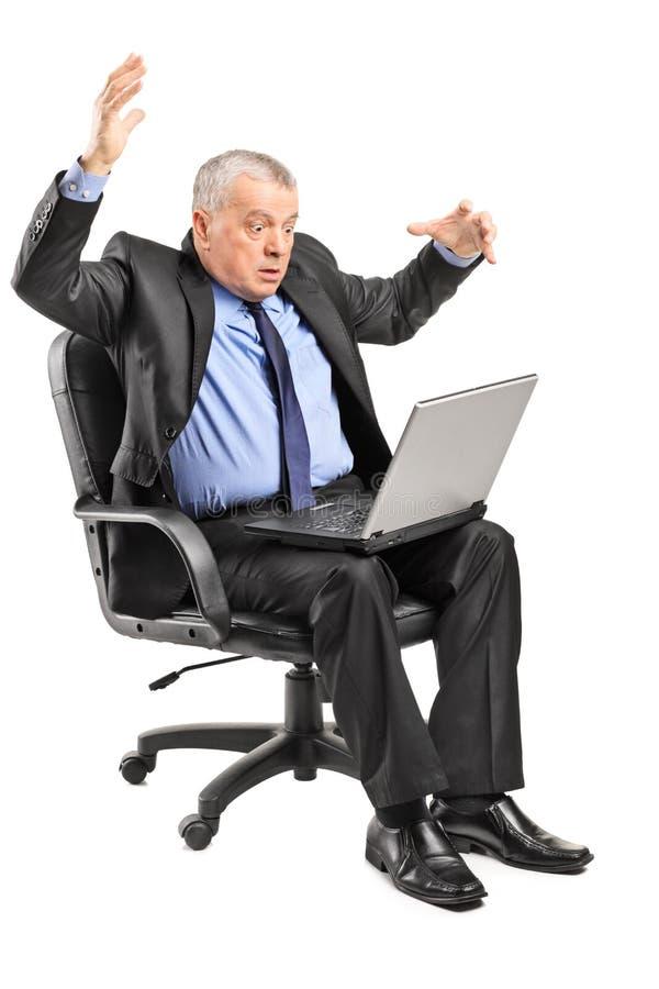 Chockad affärsman som har problem med en bärbar dator royaltyfri bild