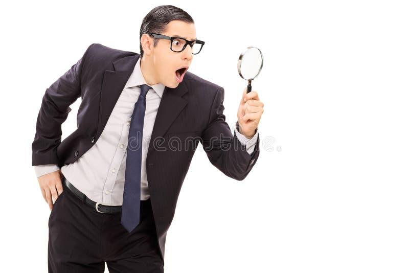 Chockad affärsman som ser till och med en förstoringsapparat fotografering för bildbyråer