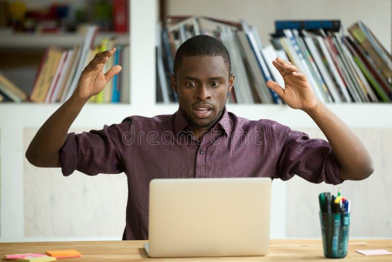 Chockad afrikansk amerikankontorsarbetare som ser bärbar datorskärmen arkivfoton
