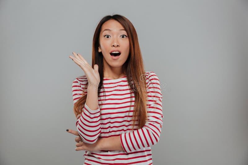 Chockad asiatisk kvinna i tröjan som ser kameran arkivbild