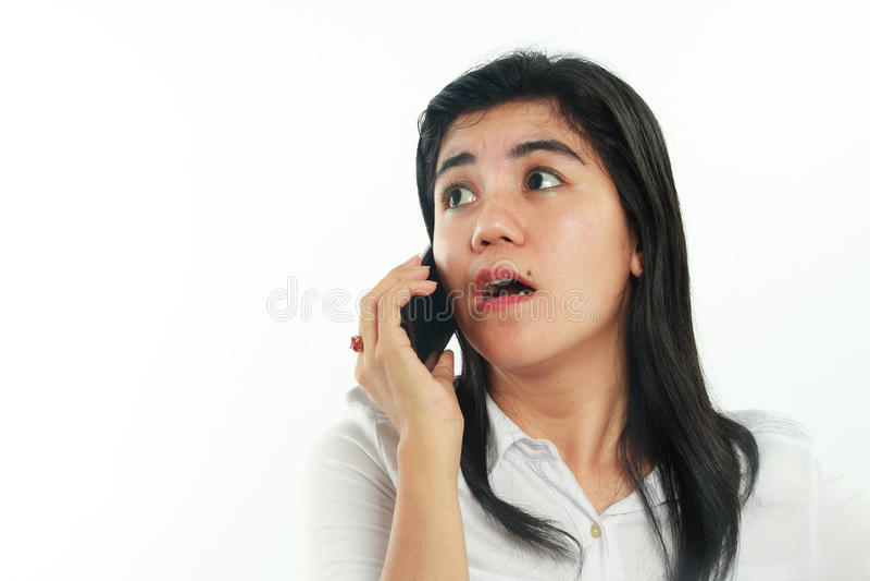 Chockad asiatisk kvinna med hennes smarta telefon arkivbild