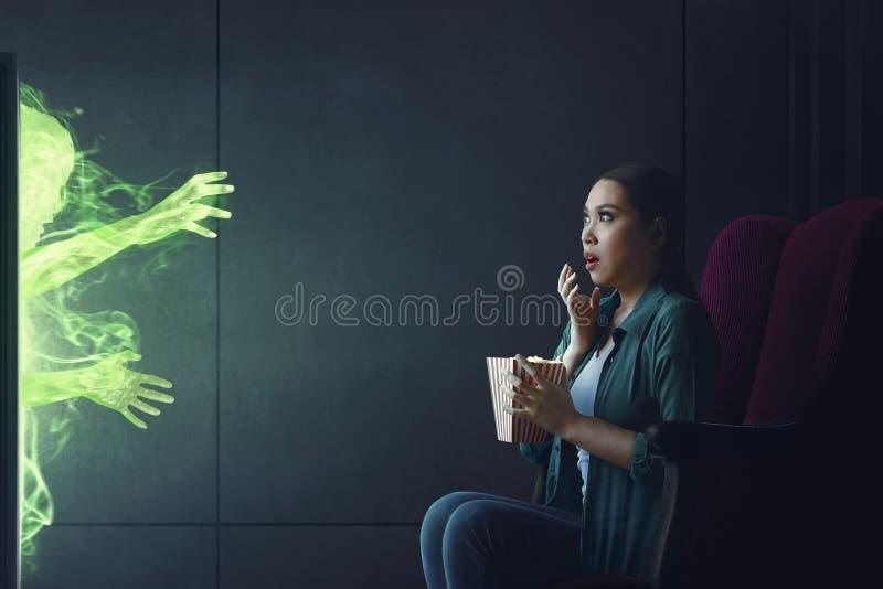 Chockad asiatisk kvinna som håller ögonen på läskig film med popcorn fotografering för bildbyråer