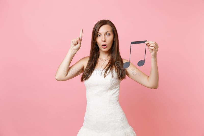 Chockad brudkvinna i bröllopsklänning som pekar det isolerade pekfingret upp den musikaliska anmärkningen för håll som väljer per arkivfoto