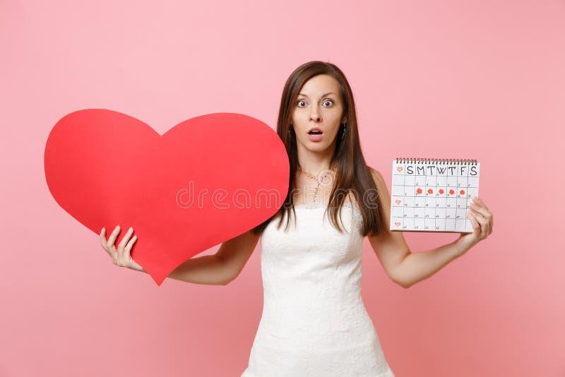 Chockad brudkvinna i den vita bröllopsklänningen som rymmer den kvinnliga periodkalendern för tom tom röd hjärta för att kontroll royaltyfria bilder