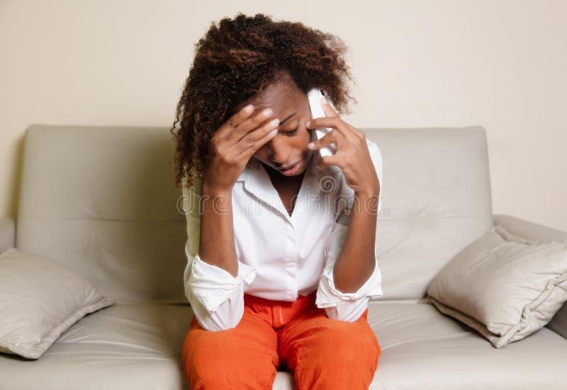 Chockad dåliga nyheter för afrikansk amerikankvinnahäleri på telefonen royaltyfri bild