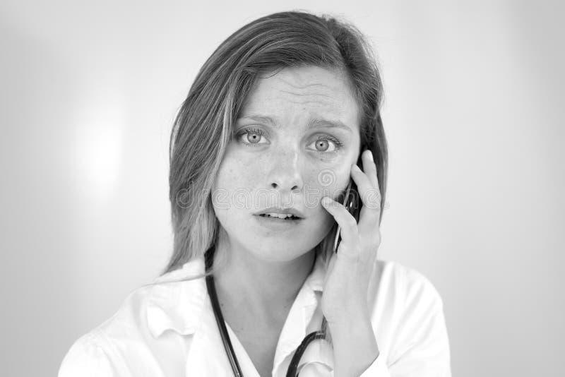 Chockad doktor för ung kvinna på telefonen som får ledsen arkivbild