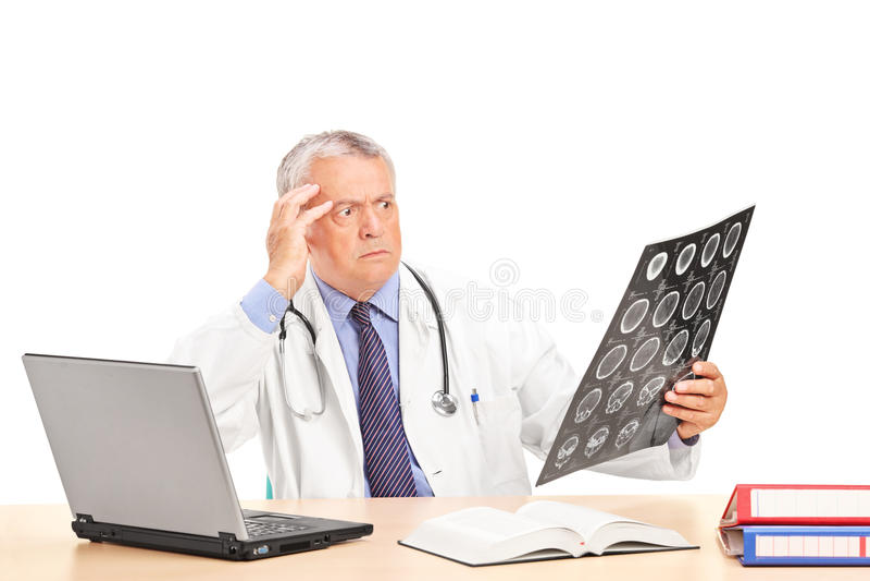 Chockad doktor som ser en röntgenstråle som placeras på en tabell royaltyfria bilder