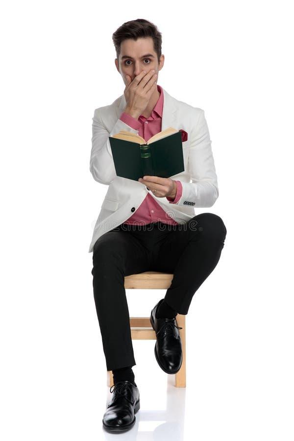 Chockad elegant man som sitter och läser en spännande bok royaltyfria foton