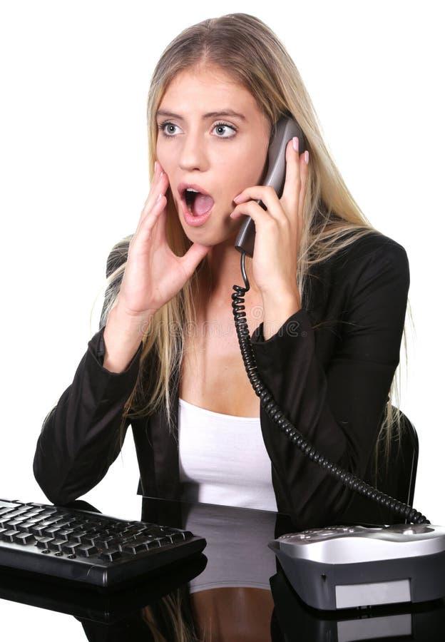 Chockad eller förvånad blond kontorsdam på hennes skrivbord arkivfoton