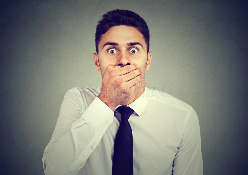 Chockad förskräckt ung man som täcker hans mun med hans hand arkivfoton