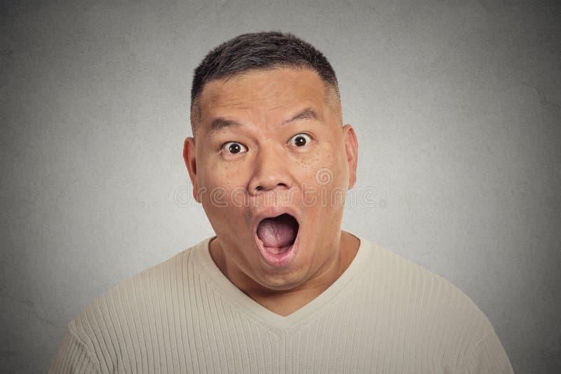 Chockad förvånad man för Headshot som isoleras på grå bakgrund royaltyfri bild