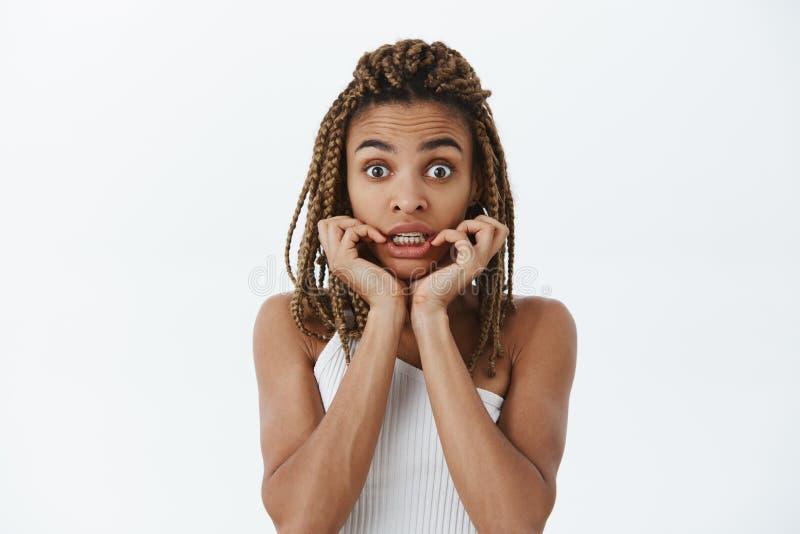 Chockad flicka som reagerar till att oroa nyheterna Stående av den förvånade och häpna mållösa mörkhyade kvinnan med dreadlocks royaltyfri fotografi