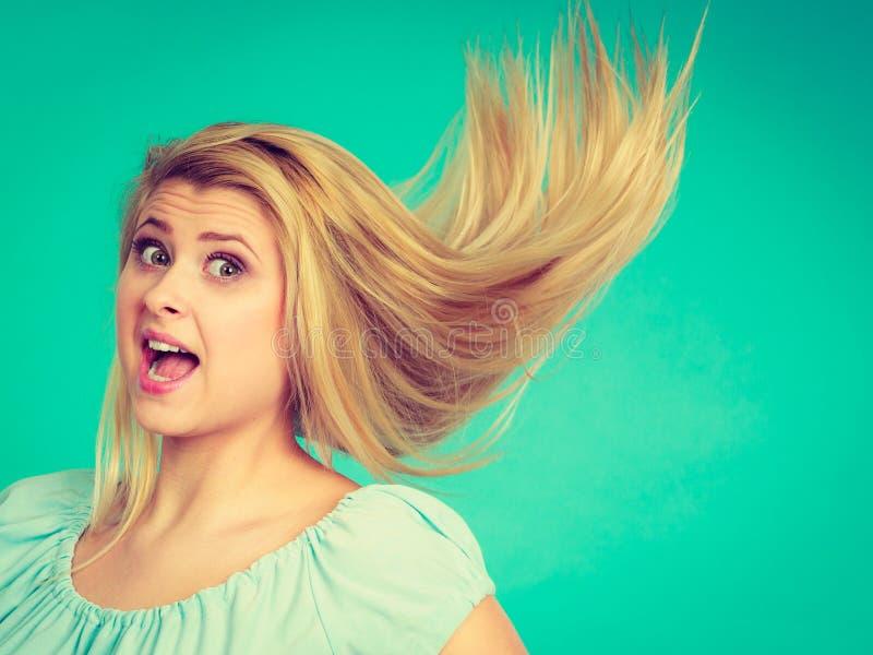 Chockad häpen blond kvinna med galet windblown hår arkivbilder
