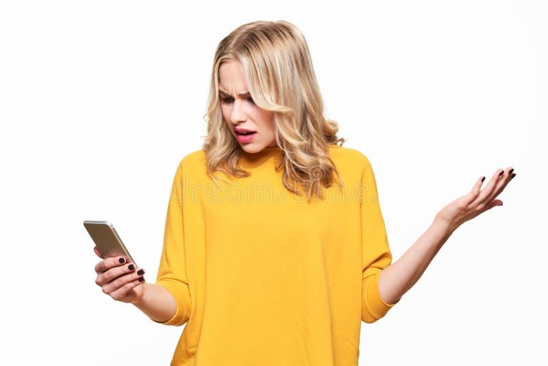 Chockad ilsken ung kvinna som ser hennes mobiltelefon i misstro Kvinna som stirrar på det chockerande textmeddelandet på hennes t fotografering för bildbyråer