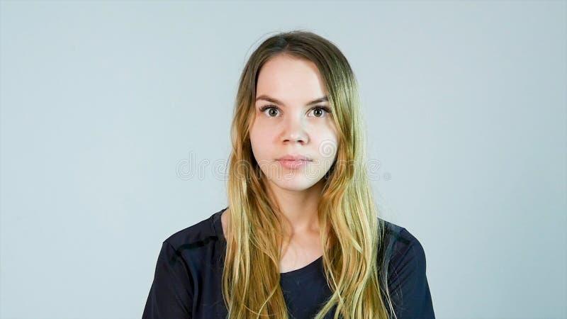 Chockad kvinna Rörande framsida för ung kvinna med händer och stirra på kameran, medan stå mot vit bakgrund arkivfoton