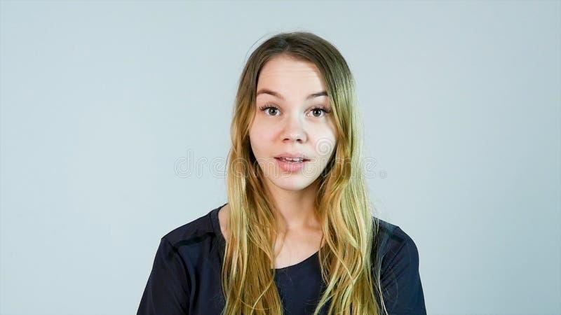 Chockad kvinna Rörande framsida för ung kvinna med händer och stirra på kameran, medan stå mot vit bakgrund fotografering för bildbyråer