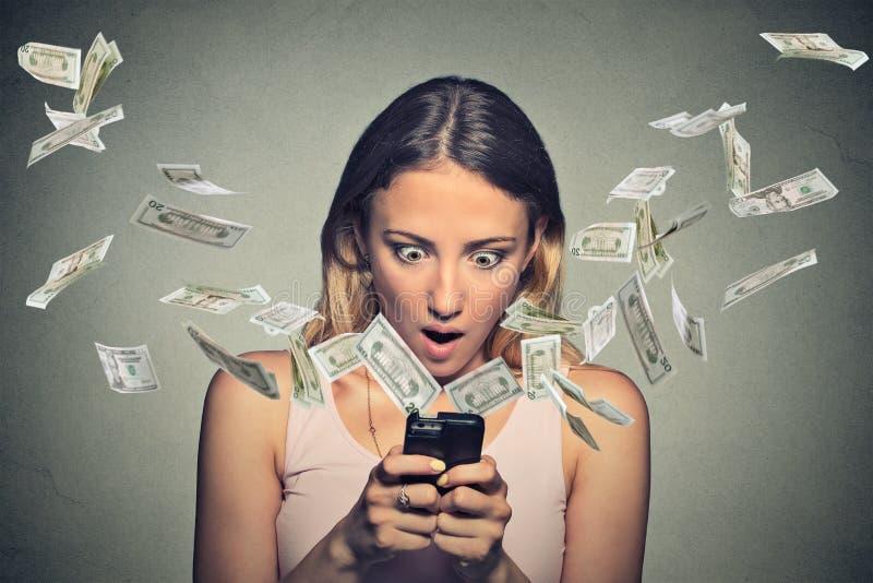 Chockad kvinna som använder smartphonedollarräkningar som flyger i väg från skärmen royaltyfri fotografi