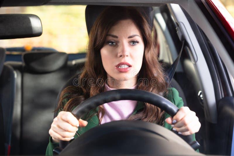 Chockad kvinna som k?r bilen arkivfoto