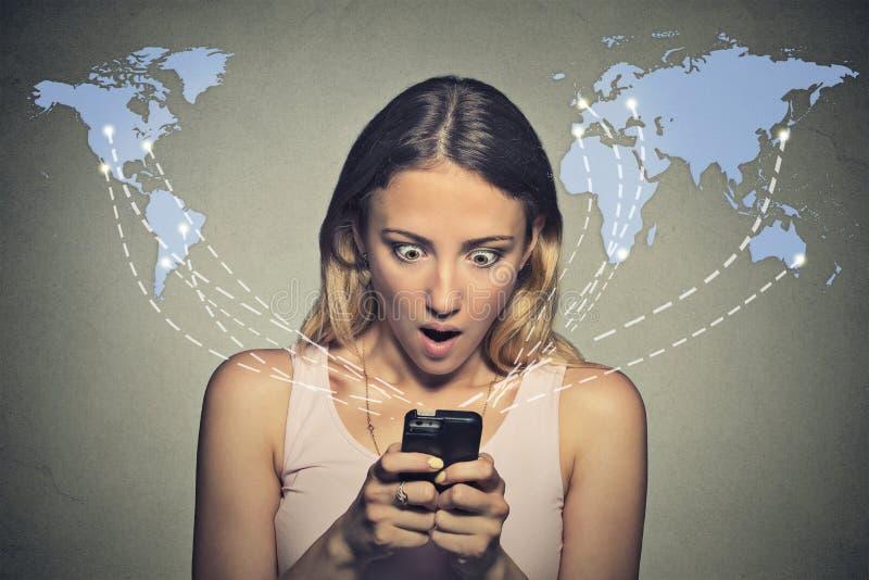 Chockad kvinna som ser hennes smarta telefon som ser dåliga nyheter eller foto royaltyfri foto