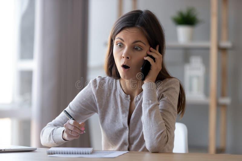 Chockad kvinna som talar på telefonen som hör otrolig nyheterna fotografering för bildbyråer