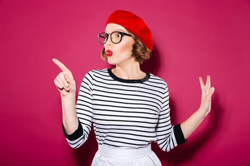 Chockad ljust rödbrun kvinna i glasögon som bort pekar och ser royaltyfria foton