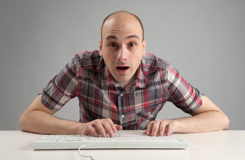 Chockad man som använder tangentbordet arkivfoto