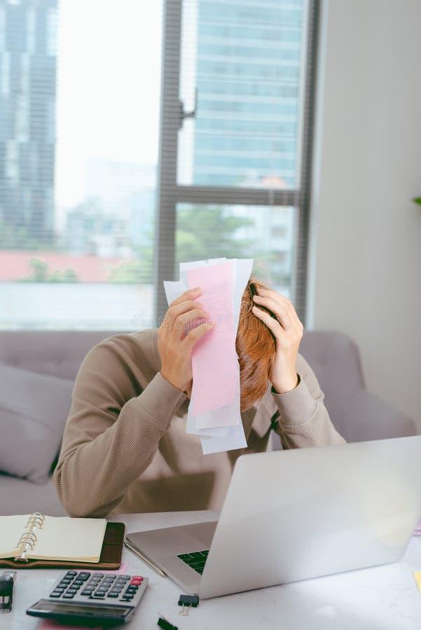 Chockad man som rymmer några dokument på soffalivingroom royaltyfri foto