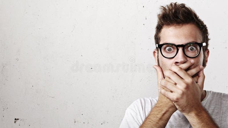 Chockad man som täcker hans mun med händer arkivbilder