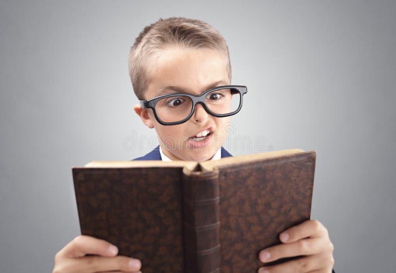 Chockad och förvånad ung utövande affärsmanpojke som läser en bok royaltyfri foto
