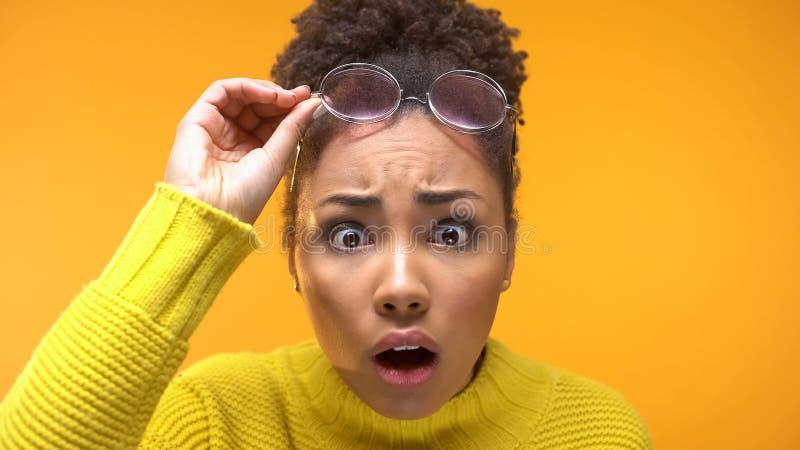 Chockad svart kvinnlig seende kamera som märker första skrynklor, hudomsorg, överraskning royaltyfri foto