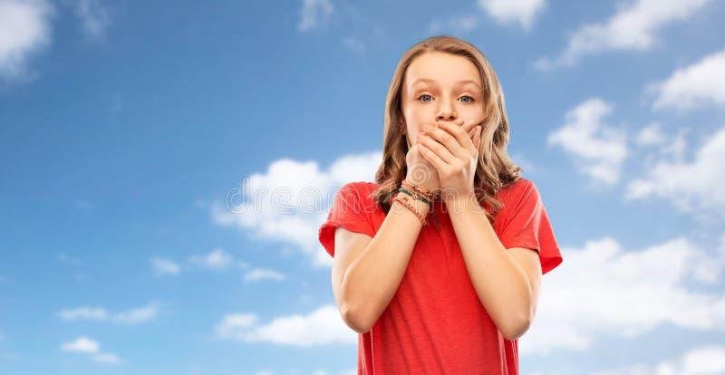 Chockad tonårs- flicka som täcker hennes mun över himmel royaltyfria bilder