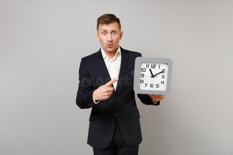 Chockad ung affärsman i den klassiska svarta dräkten, skjorta som pekar pekfingret på den fyrkantiga klockan i handen som isolera arkivfoto