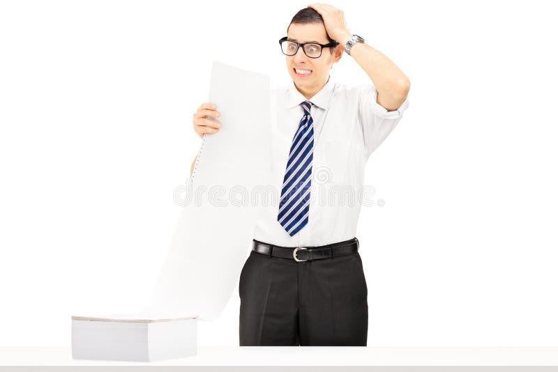 Chockad ung businessperson som ser den mycket dyra räkningen arkivbild