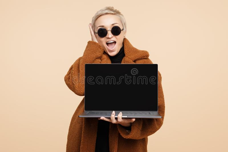 Chockad ung hipsterkvinna med blont kort hår som bär ett lag och solglasögon som rymmer en isolerade dator eller bärbar dator royaltyfri bild