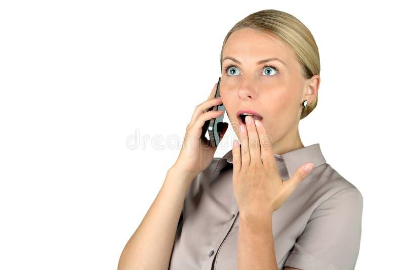 Chockad ung kvinna som talar på mobiltelefonen arkivbilder