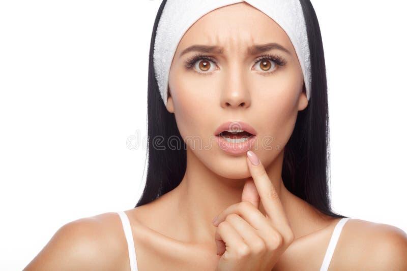 Chockad ung kvinna som trycker på hennes kanter arkivfoto