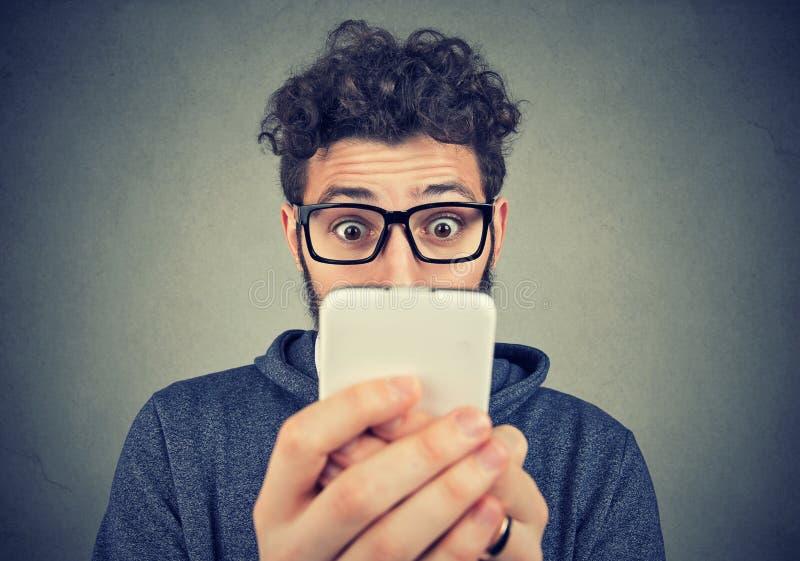 Chockad ung man som ser smartphonen arkivfoton