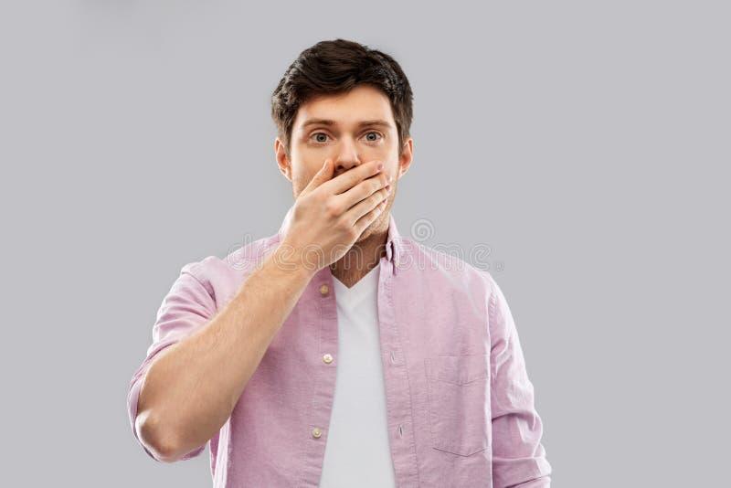 Chockad ung man som täcker hans mun vid handen fotografering för bildbyråer