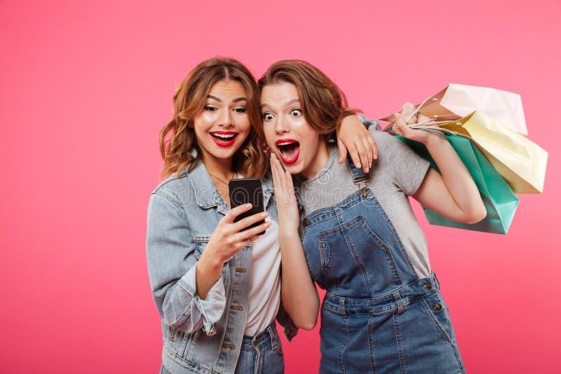Chockade två kvinnavänner som rymmer shoppingpåsar genom att använda mobiltelefonen arkivbild