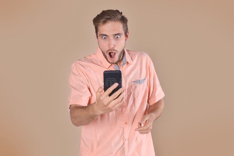 Chockat anseende för ung man som isoleras över beige bakgrund, genom att använda mobiltelefonen arkivfoto