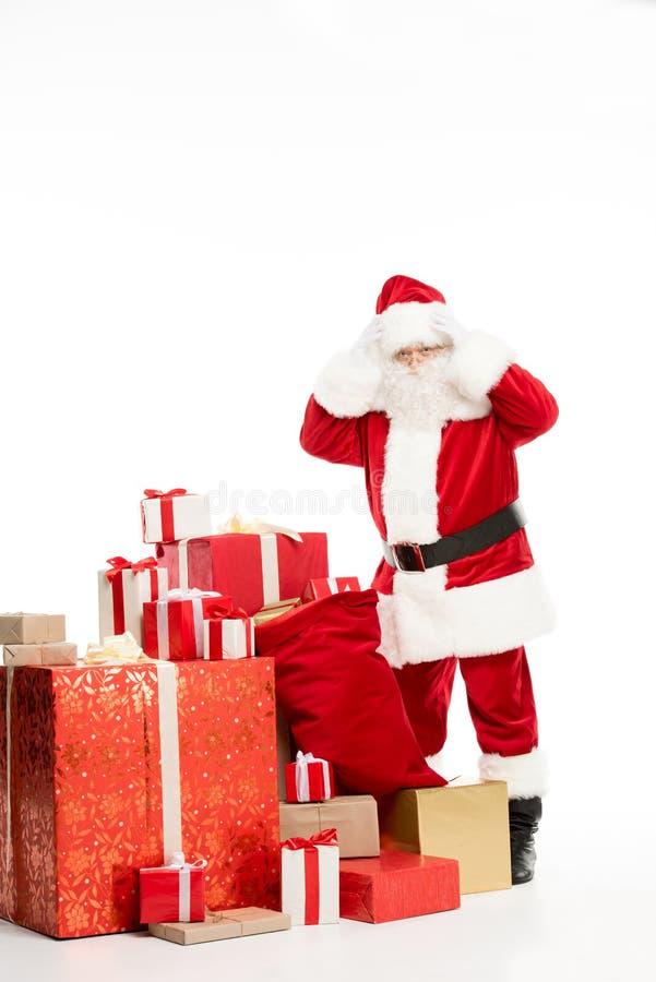 Chockat Santa Claus anseende med julgåvor arkivfoton