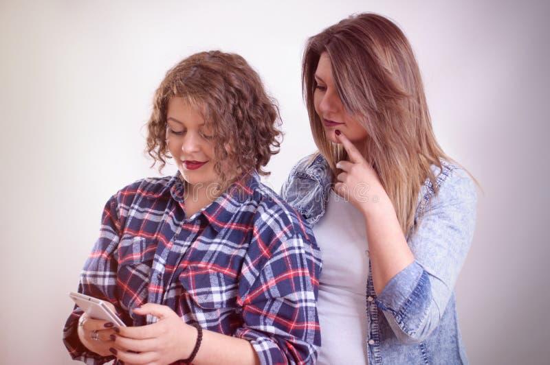 Chockat stirra för två flickor på smartphonen royaltyfria foton