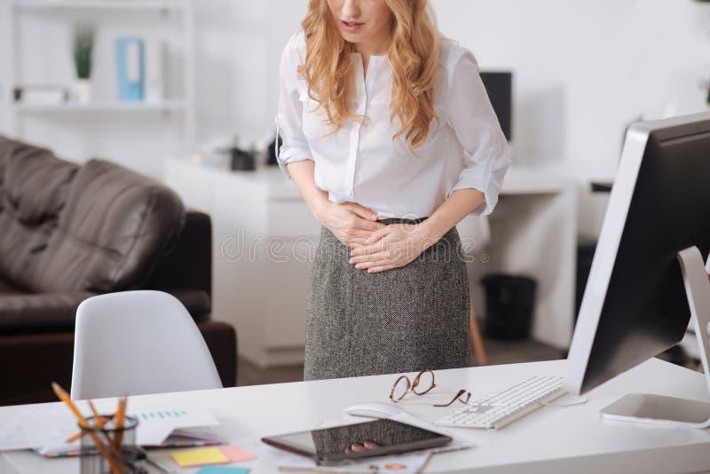 Chockat ungt affärskvinnalidande från magknip i kontoret arkivbilder
