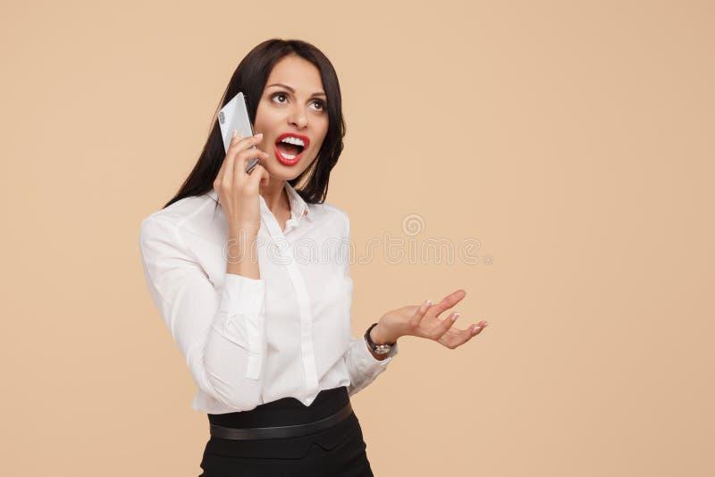 Chockat ungt modernt samtal för affärskvinna på smartphonen över beige bakgrund fotografering för bildbyråer